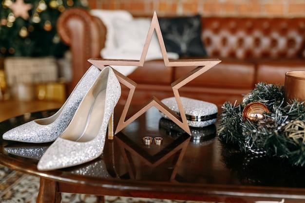 Свадебные туфли и свадебная атрибутика обручальные золотые кольца свадебный букет на столе