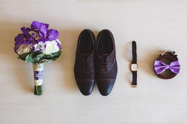 結婚式の靴、ベルト、時計、白い表面に花束。結婚式の日に新郎のためのアクセサリー。