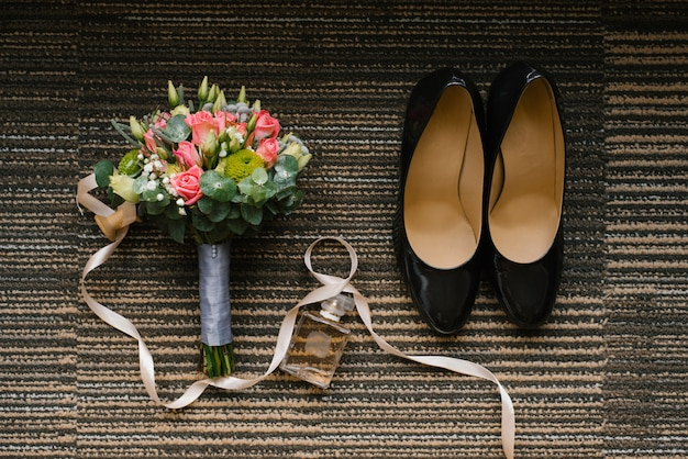 Wedding shoes, birde bouquet of roses and eucalyptus, a jar of toilet water