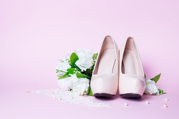 Wedding shoes and bouquet lying on pink. close up