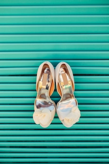 Wedding shoes of the bride on a blue wooden background