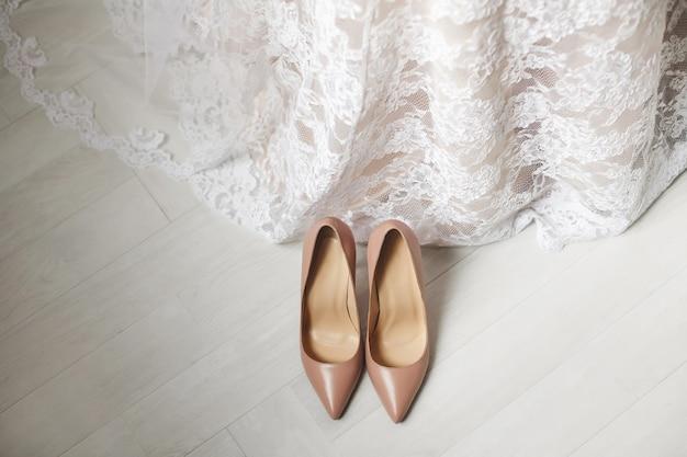 Свадебные туфли кремового цвета белого цвета на полу. свадебное платье.