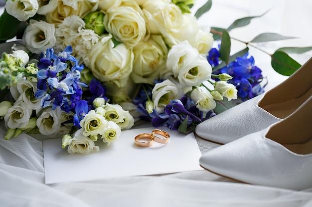 Свадебные туфли для невесты. белые туфли на каблуках возле обручальных колец, свадебные украшения. концепция брака