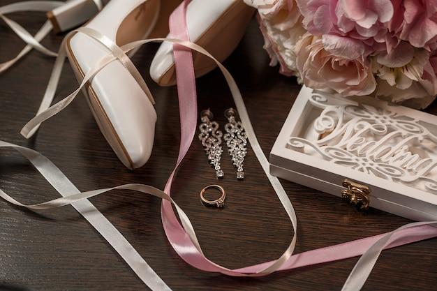 花嫁のための結婚式の靴。結婚指輪、結婚式の宝石の近くの白いかかとの高い靴。結婚の概念
