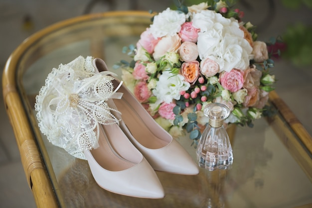 Wedding shoes with bouquet of flowers and perfume