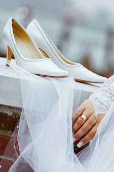 Wedding shoes with heels are hanging on a white fence before the bride puts them on for her wedding ceremony.
