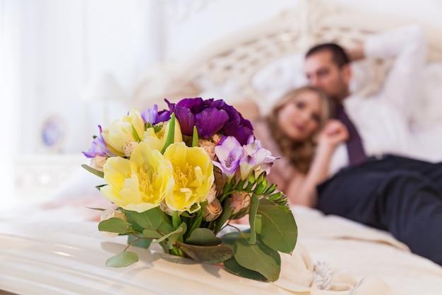 Свадебный снимок жениха и невесты фокусируется на букете. молодая свадебная пара наслаждается романтическими моментами. свадебные торжества.