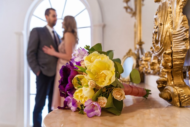 新郎新婦の結婚式のショットは花束に焦点を当てるロマンチックな瞬間を楽しんでいる若い結婚式のカップル