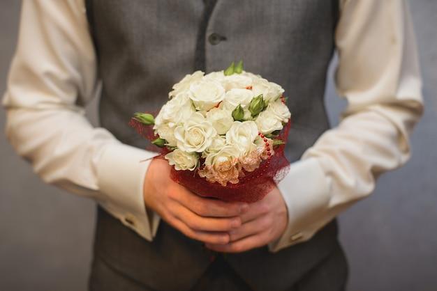 新郎の手に白いバラの結婚式の小さなかわいい花束