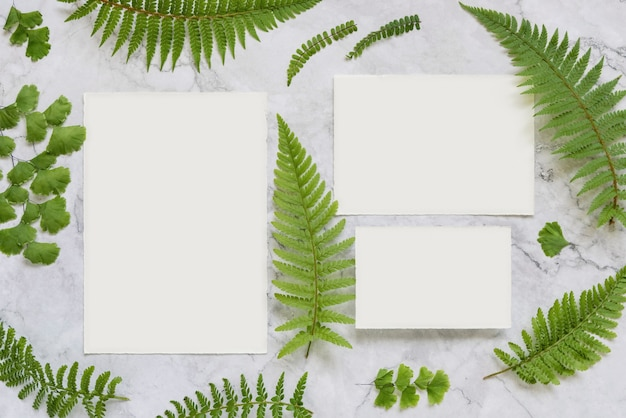 Wedding stationery set of cards and envelope decorated with fern leaves top view on marble table. tropical mock-up scene with blank paper card flat lay