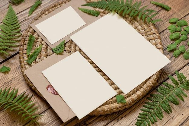 Свадебный канцелярский набор карт и конверт, украшенный листьями папоротника, рядом с деревянным столом. тропический макет сцены с плоской планировкой пустой бумажной карты