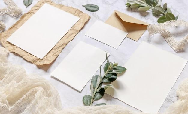 Свадебные канцелярские принадлежности на мраморном столе, украшенном ветками эвкалипта и лентами, макет