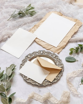 Свадебные канцелярские принадлежности на мраморном столе с эвкалиптовыми ветками и лентами, макет сцены