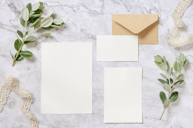 Wedding stationery set with envelope laying on a marble table decorated with eucalyptus branches and ribbons. mock-up scene with blank paper greeting cards. feminine flat lay