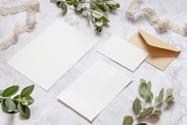 Wedding stationery set with envelope laying on a marble table near eucalyptus branches and ribbons