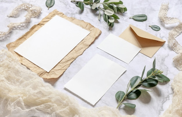 Свадебный канцелярский набор с конвертом на мраморном столе, украшенном ветками эвкалипта и лентами. макет сцены с пустыми бумажными поздравительными открытками. женский крупный план