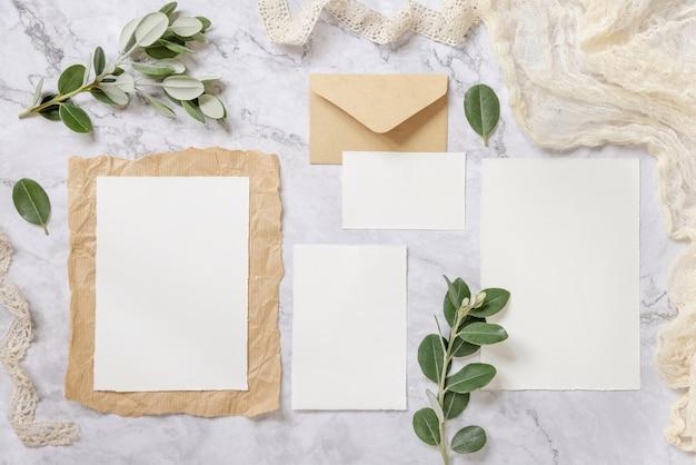 Свадебный канцелярский набор с конвертом на мраморном столе, украшенном ветками эвкалипта и лентами. макет сцены с пустыми бумажными поздравительными открытками. женственная плоская планировка