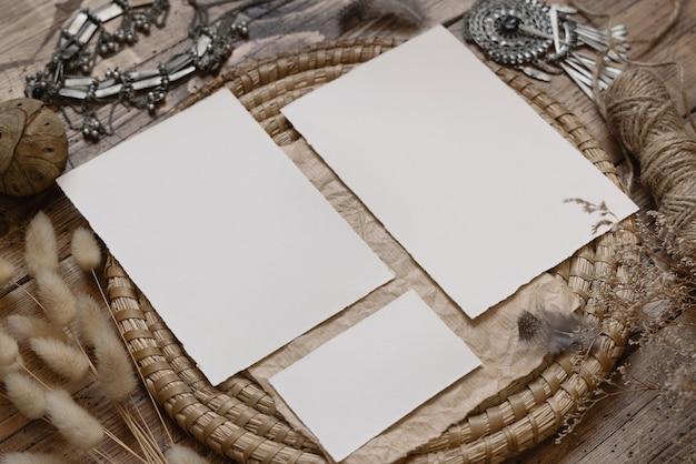 Свадебный канцелярский набор с конвертом, лежащим на деревянном столе с богемным декором вокруг. бохо макет сцены с чистыми бумажными поздравительными открытками крупным планом