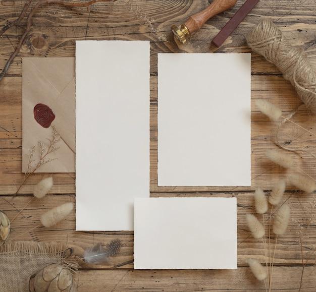Свадебный канцелярский набор с конвертом, лежащим на деревянном столе с богемным декором вокруг. макет сцены с видом сверху поздравительных открыток чистого листа. женская плоская планировка в стиле бохо