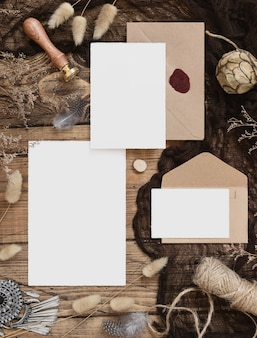 Wedding stationery set with envelope laying on a wooden table with bohemian decoration around. mock-up scene with blank paper greeting cards and dried plants top view. feminine boho flat lay