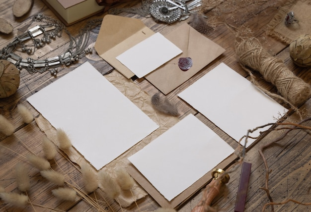 Wedding stationery set with envelope laying on a wooden table with bohemian decoration around