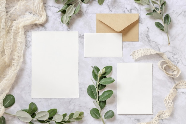 Wedding stationery set with envelope on a marble table decorated with eucalyptus branches mockup