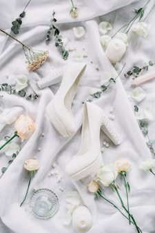 하이힐 구두, 유칼립투스 가지, 흰색 섬유에 장미 꽃이있는 결혼식 세련된 구성