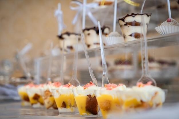 結婚式のお菓子、装飾されたテーブル、装飾とカップケーキ、おいしいケーキと珍味