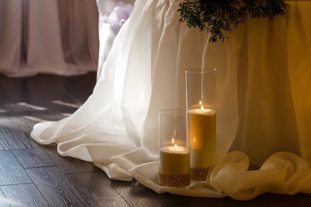 Wedding table decor with big shining candles in glass