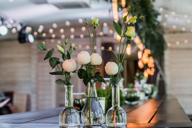 Свадебный стол оформлен в стиле бохо. украшенный деталями, композиция из цветочного пиона в стеклянных вазах