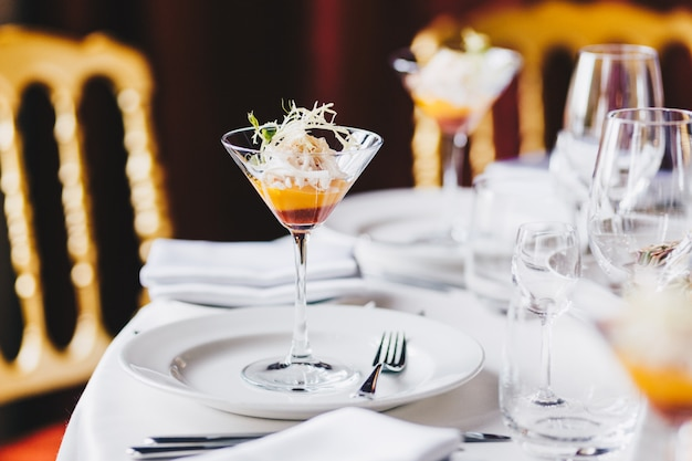 Wedding table decorated with white plates, glasses for wine and cocktail in spacious hall