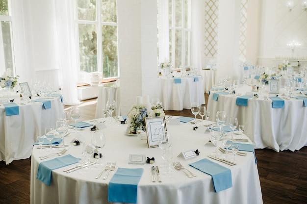 結婚式の夕食のためのレストランのテーブルの装飾のテーブルの上の青い花と結婚式のテーブルの装飾。