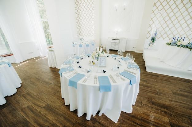 결혼식에서 저녁 식사를 위해 레스토랑 테이블 장식의 테이블에 푸른 꽃과 웨딩 테이블 장식.