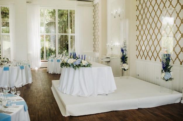 결혼식에서 저녁 식사를 위해 레스토랑 테이블 장식의 테이블에 푸른 꽃과 웨딩 테이블 장식