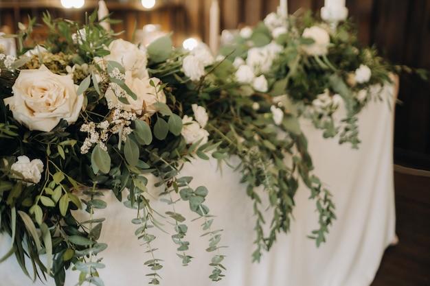 城のテーブルに花が飾られた結婚式のテーブルデコレーション、キャンドルライトによるディナーのテーブルデコレーションキャンドル付きディナー