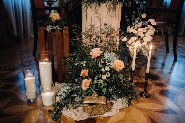 城のテーブルに花が飾られた結婚式のテーブルデコレーション、キャンドルライトによるディナーのテーブルデコレーション。キャンドルでディナー。