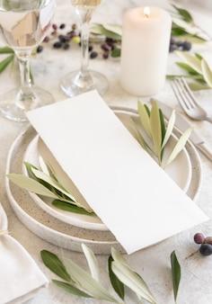 Свадебный стол с открыткой, украшенной оливковыми ветвями