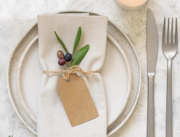 Свадебный стол с визитной карточкой и фарфоровыми тарелками, украшенными оливковыми ветвями, вид сверху. элегантный современный шаблон с горизонтальной пустой бумажной картой. средиземноморский плоский макет, копия пространства