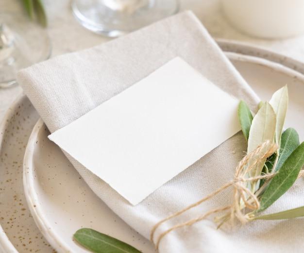 올리브 가지로 장식된 카드가 있는 웨딩 테이블 장소