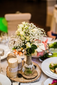 Wedding table in the restaurant decorated with flowers in rustic style