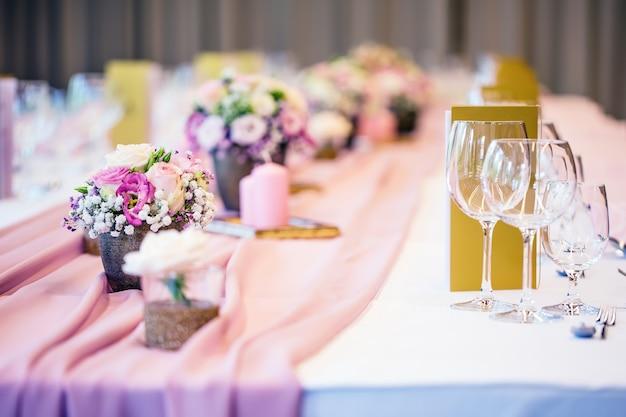 結婚式のテーブルセッティング。いくつかのお祝いのイベント、パーティーや結婚披露宴のための花とガラスのカップがセットされた美しいテーブル。