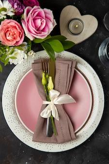 Сервировка свадебного стола концепция тарелка столовые приборы на льняной салфетке и цветы вид сверху вертикальное фото