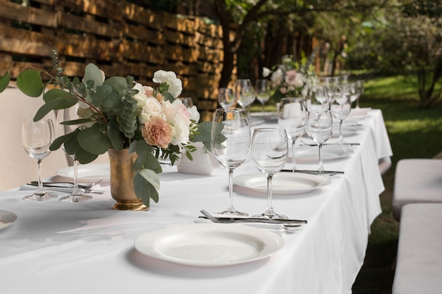 Wedding table setting decorated with fresh flowers in a brass vase