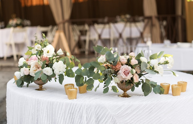 Wedding table setting decorated with fresh flowers in a brass vase.