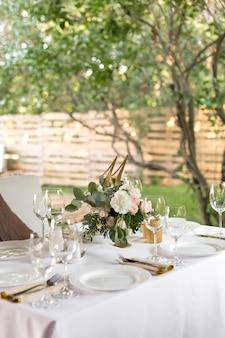 황동 꽃병에 신선한 꽃으로 장식 된 웨딩 테이블 설정. 웨딩 플로리스트 리. 녹색 자연을 바라 볼 수있는 야외 손님을위한 연회 테이블. 장미, eustoma 및 유칼립투스 잎이있는 꽃다발