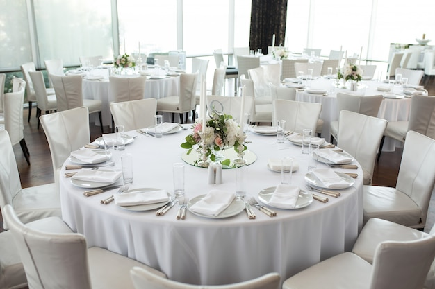 Wedding table setting decorated with fresh flowers.
