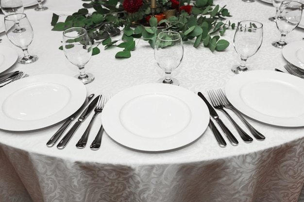 The wedding table setting is decorated with fresh flowers in a brass bowl. banquet table for guests