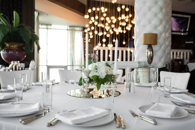 Wedding table setting is decorated with fresh flowers and white candles. wedding floristry. bouquet with roses