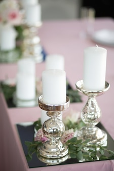 The wedding table setting for the newlyweds is decorated with silver candlesticks, white candles.