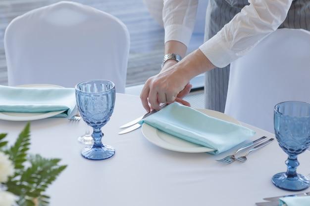 結婚式のテーブルセッティング。グレーのスーツと白いシャツのウェイターがテーブルを提供